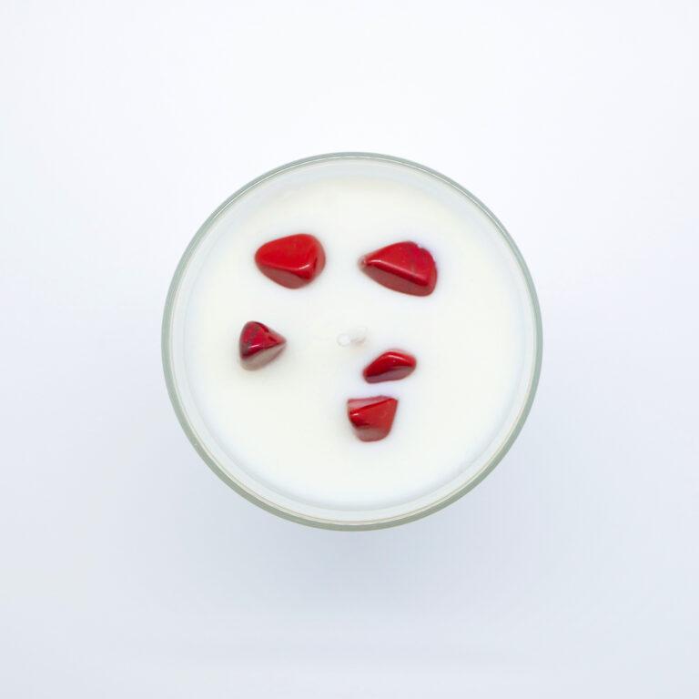 Bougie parfumée artisanale incrustée de pierre naturelle de Jaspe Rouge. Le Jaspe Rouge est une pierre d'action et d'initiative qui ancre naturellement l'énergie tout en stimulant en douceur. Cette bougie d'un parfum naturel de Grasse 100% a une cire naturelle 100% végétale, sans OGM, pesticide, CMR paraben et paraffine.